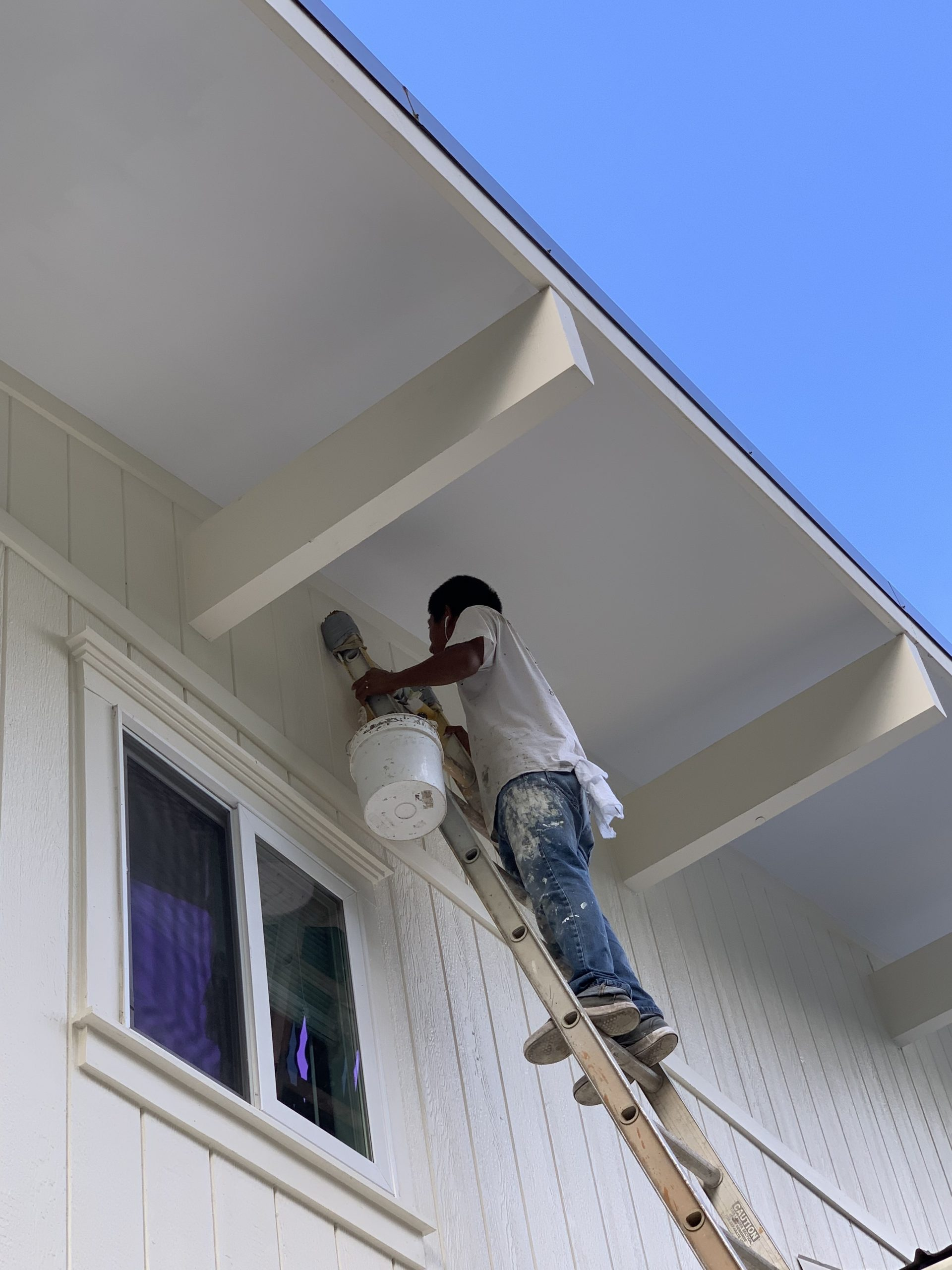 Brown Painting Inc. in Kailua Kona Exterior Painting with an industrial motor lift for tall house professional painting in Kailua Kona, Hawaii.